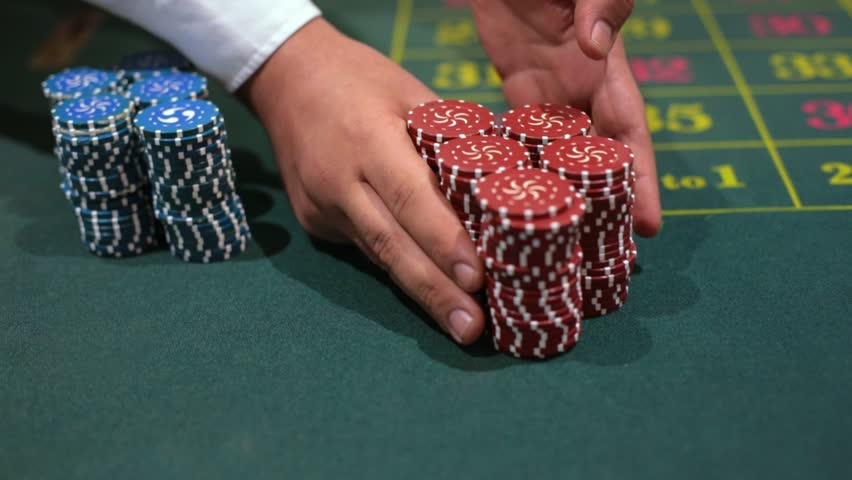 dealer poker player with chips at casino table