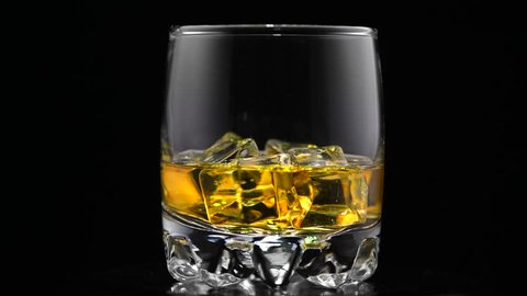 Whiskey Bourbon with ice. Rotated glass of whisky on black background. Glass of rum alcohol close-up. Isolated on black. 4K UHD video