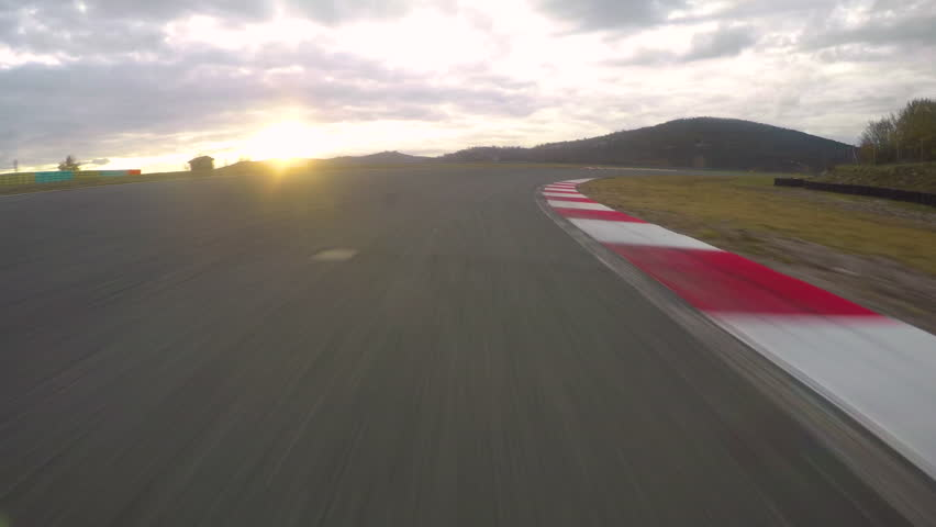 POV: Racing a car down the empty asphalt circuit on a beautiful golden evening. Cool first person view of racing a fast on a scenic racetrack at sunset. Picturesque landscape and the morning sky.