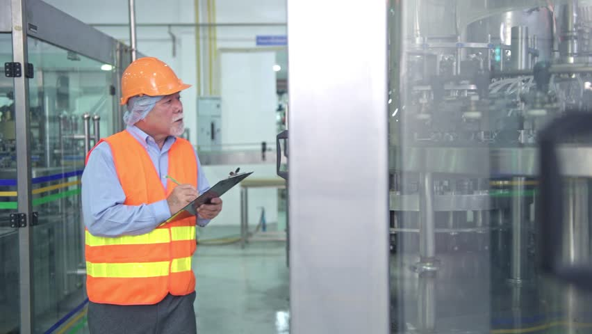 Quality inspection in factory. Senior chinese quality assurance team inspecting a liquid filling bottle machine in factory using TQM, TPM methodology. Excellence manufacturing concept. | Shutterstock HD Video #1016349199