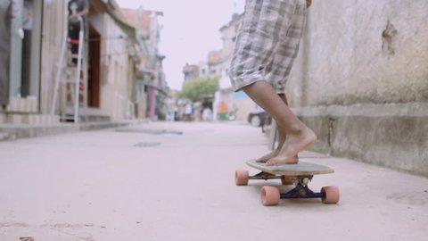 Child Skateboards Through Favela Slow Motion