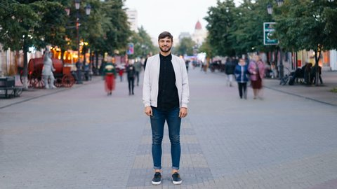 Time-lapse of bearded young man standing in the street in big city and looking at camera then moving back while people are moving around him quickly.