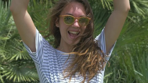 Portrait of funny girl. Woman going crazy. Raising her hands and shout. Showing peace sign. Posing on exotic green background. In casual clothes and sunglasses. 4k
