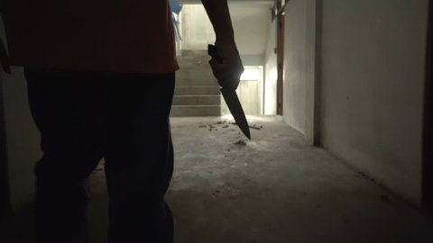 Silhouette of a man carry a knife walking in an Abandoned house