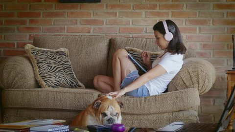 Online Shopping. Dolly shot of Hispanic young woman playing with dog surfing on the internet with digital tablet and listening to online music