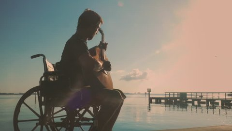 Man in wheelchair playing acoustic guitar at beach pier