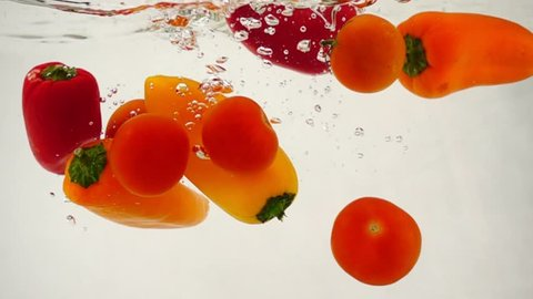 Made dish fresh vegetables, pepper and cherry tomatoes dropping in water, slow motion close-up