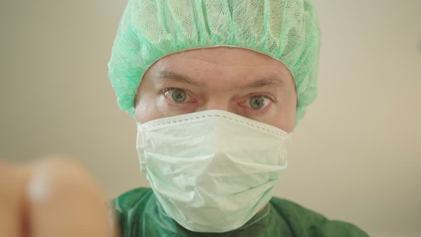 Doctor in op clothing operates with his hands, closeup, from the patient's point of view | Shutterstock HD Video #1016450059