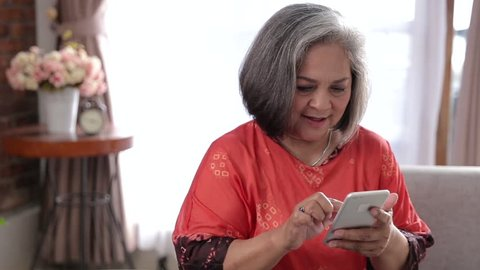 Cheerful senior asian woman using her smart phone at home