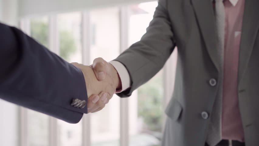 Slow motion - Handshake to seal a deal after a job recruitment meeting. Two asian confident businessman shaking hands during a meeting in the office, success, dealing, greeting and partner concept.