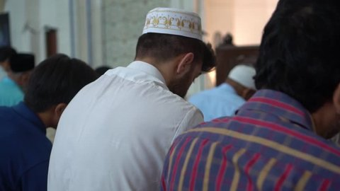Footage of Muslim men praying in a mosque.