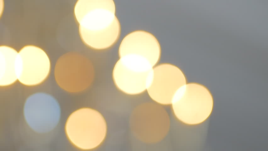 Out of focus gold and whit lights pan right to left