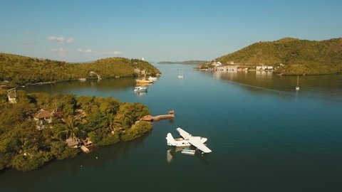 aerial white Seaplane in the sea bay. hydroplane on the water surface near the shore Travel concept, Aerial footage.