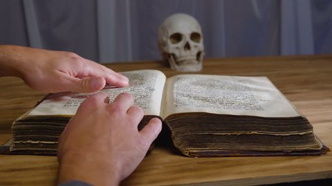 the magic rite. Ancient book and human skull. Concept for Halloween