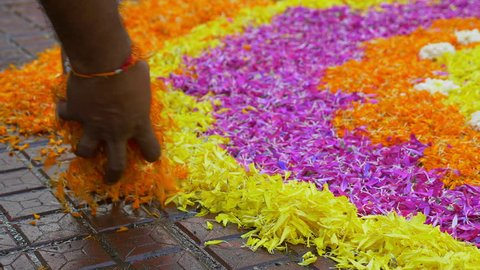 Rangoli with flower petals being created by Rangoli artist on occasion of Ganesh Festival Mumbai, Maharashtra, India.