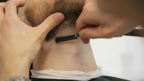 Professional barber with open cutthroat razor shave the beard in the Barbershop. Man hairdressing with straight razor cuts the hair on face. Slow Motion. Close Up