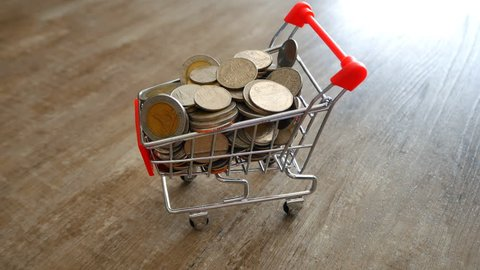 Shopping cart and coins on old wooden floor , Business and finance concept