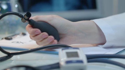 Measure blood pressure. Close up of woman hand check heart rate with digital measurement equipment. Blood pressure check. Nurse hand measuring pressure