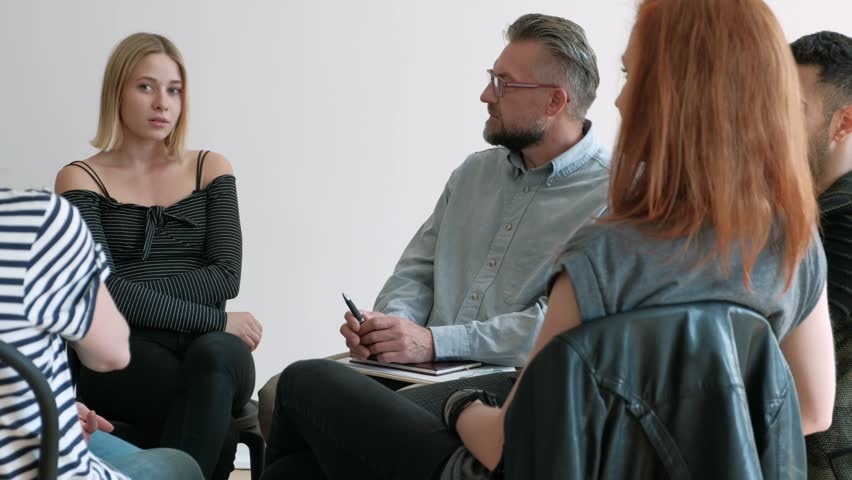 Young woman talking with therapist during meeting of support group