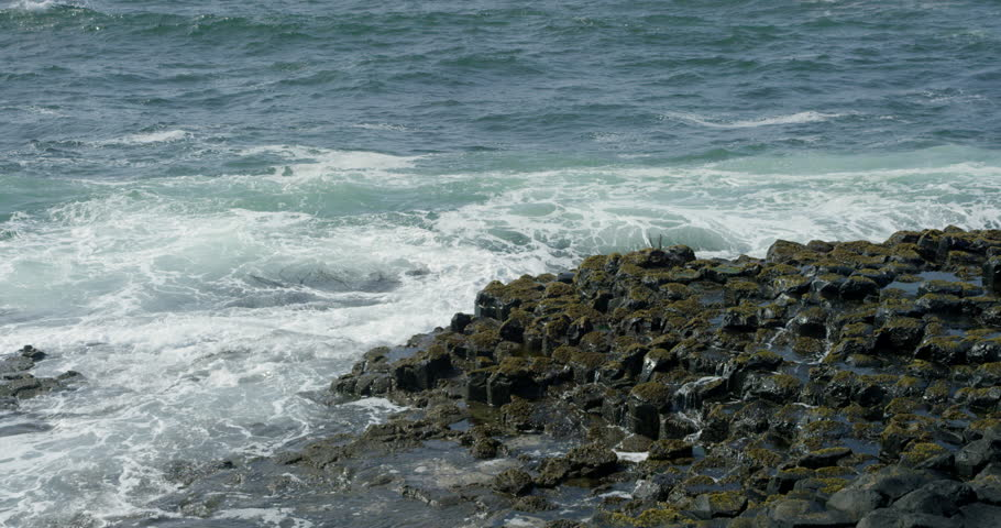 Waves breaking along the hexagon shaped shoreline of the Giant's Causeway in Ireland.