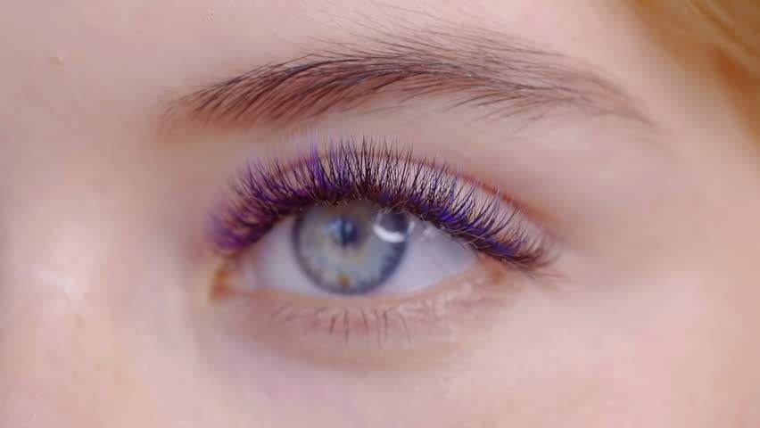 Close - up of female eye with eye shadow and long multi-colored eyelashes, covered with mascara
