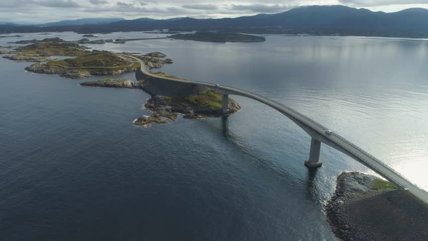 Cars are Going on Storseisundet Bridge. Atlantic Ocean Road in Norway. Aerial View. Drone Orbits Around, Camera Tilts Up