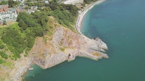 Zooming out with the drone over the landscape of Torquay. The beach and cliffs are visible below. Buildings next to woodland are visible as well.