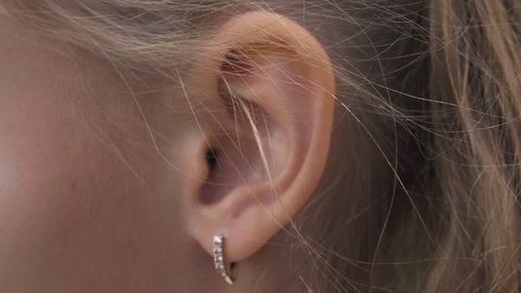 Female ear with earring close up. Ear of woman blonde with decorative piercing