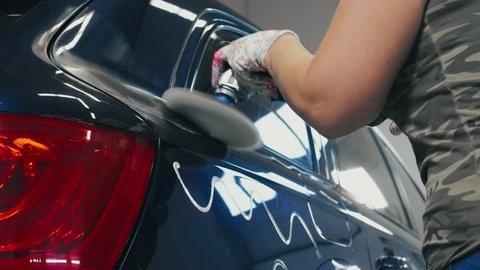 Female worker doing car body polishing with polisher in auto service. Woman worker making waxing car at car wash. Car body work