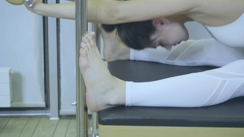 Pilates. Woman in white clothes practicing stretching exercise on reformer in gym.