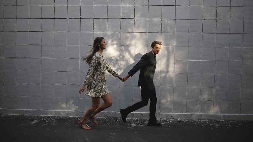 A young man and woman running holding hands in a city park. Love couple having a romantic walk.