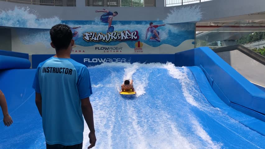 Kuala Lumpur, Malaysia - September 20 2018: Kids and an instructor at an indoor surfing facility, Flow Rider in a shopping complex, One Utama, Damansara.  | Shutterstock HD Video #1016749369