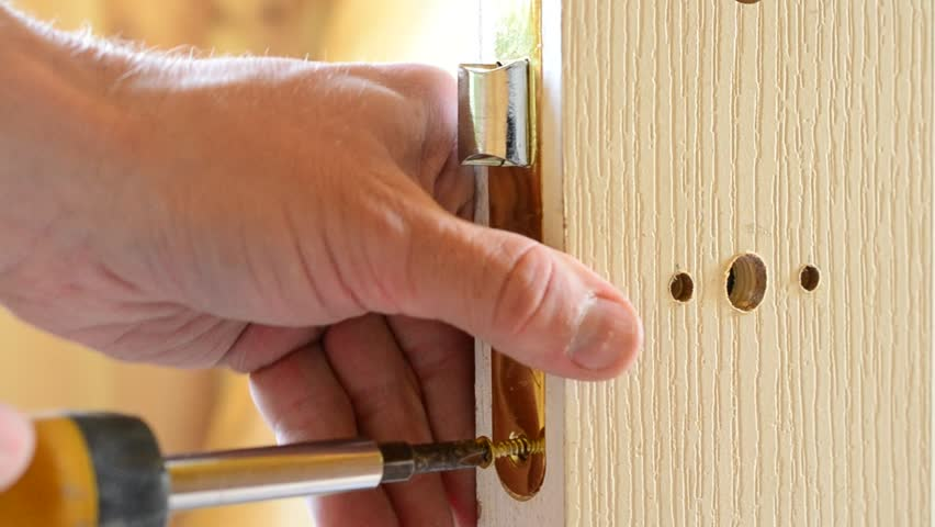 Closeup of human hands mounting a yellow golden color mortise door lock - inserting mortice doorlock into a pocket cut into white door and fixing it with screws with a screwdriver | Shutterstock HD Video #10167926