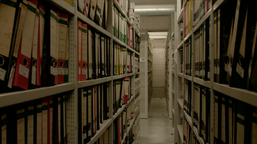 In an archive, between two shelf walls, the camera moves through many files The image can be used for the integration of archive texts in films and reports. Thanks to the 50 frames it can slowed down. | Shutterstock HD Video #1016795269
