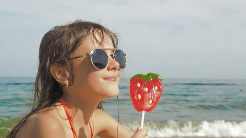 Child with a lollipop. Little girl with a big candy on the beach.