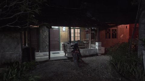 Indonesian village hut at night with motorbike parked out front