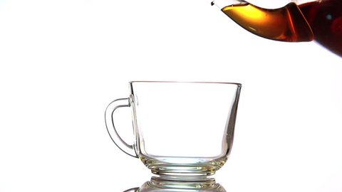 Tea pouring. Tea being poured into glass transparent tea cup. Isolated on white background. Tea time. Transparent glass teapot and teacup. Slow motion 240 fps. 4K UHD video 3840X2160