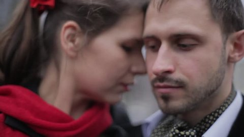 Portrait of young cute bearded man in blue velvet jacket and attractive brunette woman with red scarf and skirt performing in empty daylight winter street among dark naked trees on blurry background.