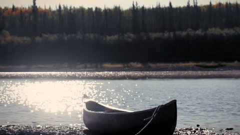 Yukon River, Yukon Territories, Alaska. Metalic canoe on a pebble beach in the sunset with the forest in teh other side of the river. Yukon River.