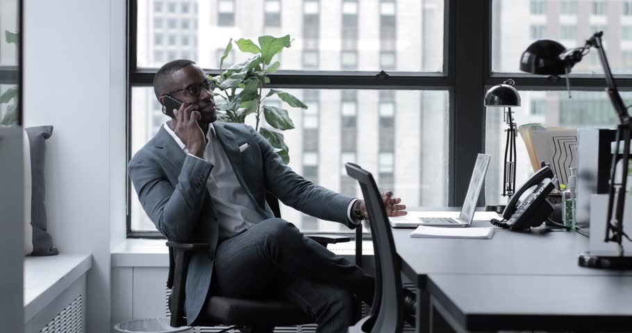 Lockdown shot of businessman answering smart phone while sitting at desk in office | Shutterstock HD Video #1016888239