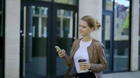 Cheerful young businesswoman surfing her mobile phone while walking down street and stopping to text back in messenger