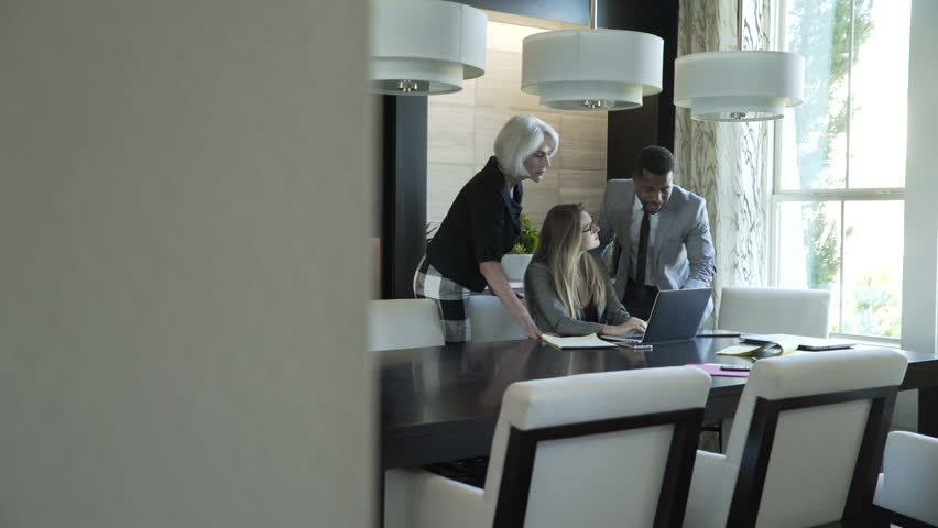 Handheld shot of business people discussing over laptop computer in meeting at board room | Shutterstock HD Video #1016891209
