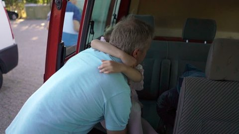 Dad carefully takes the sleeping child out of the car.