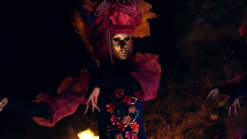 The face of the girl at the masquerade in a Venetian suit hides a mysterious mask. Dance with fire in the night. Concept idea for dance | Shutterstock HD Video #1016919889
