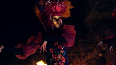 The face of the girl at the masquerade in a Venetian suit hides a mysterious mask. Dance with fire in the night. Concept idea for dance