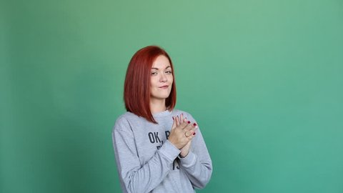 Studio clip of beautiful woman with bright dyed hair of red color wearing grey pullover with cynical message and pointing to it with hands. She is showing grimaces, flirting and winking at camera over