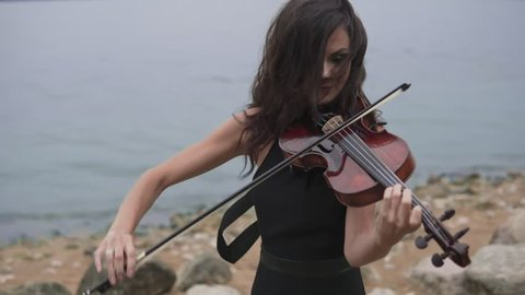 Young violinist in long black dress plays with inspiration at sea background. Beautiful girl with violin close up. Art concept in 4k