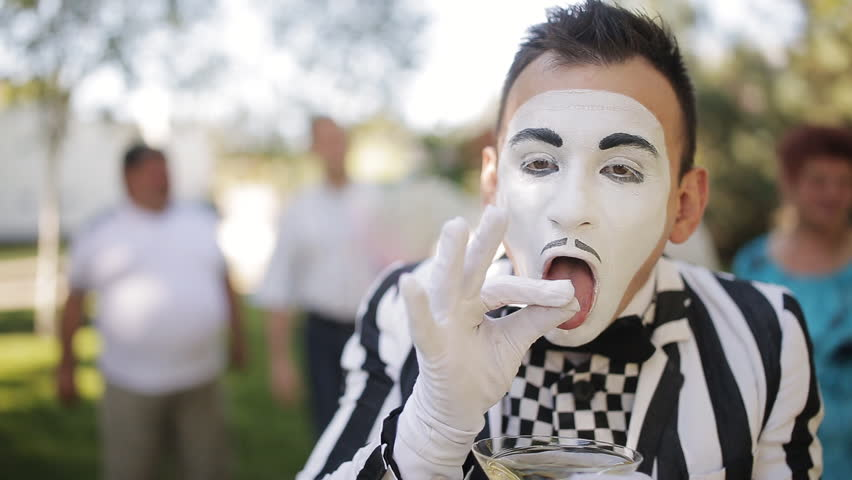 cheerful mime in a striped suit makes a grimace of a smoking person