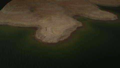 Wide high angle flyover view of women on shore of lake / Lake Powell, Utah, United States