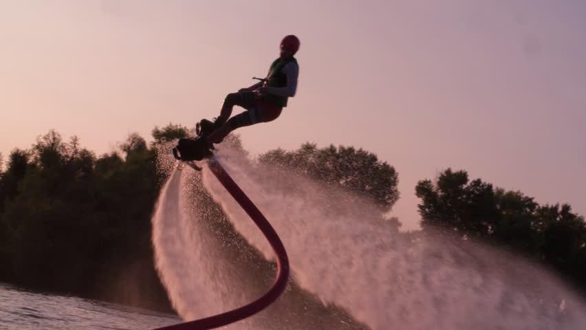Flyboarder doing tricks slow motion flying Flyboarding medium shot video #1016952289